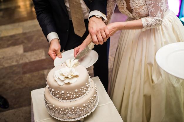 A noiva eo noivo cortar o bolo de casamento em um banquete em um restaurante