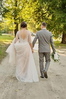 A noiva eo noivo ir para casa ao longo da estrada ao longo do campo verde