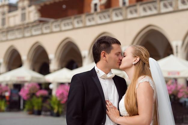 A noiva está de pé em frente ao prédio