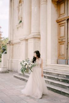 A noiva está perto das portas de uma velha igreja com um buquê de peônias de rosas brancas e