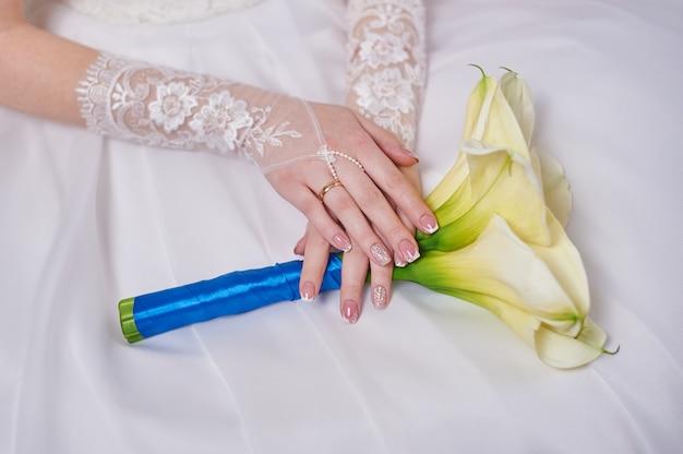 A noiva está segurando um buquê de casamento de callas.