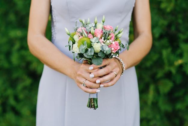 A noiva está segurando um buquê de casamento pequeno com rosas, costumes e vegetação close-up