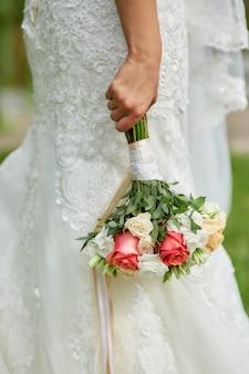 A noiva está segurando um buquê de flores bonitas