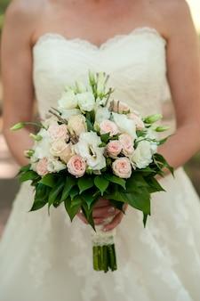 A noiva está segurando um buquê de flores naturais.