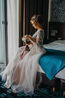 A noiva está sentada na cama do hotel.