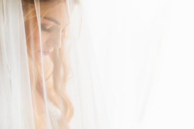A noiva fechou os olhos e tule no perfil em primeiro plano