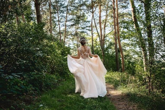 A noiva foge pela estrada da floresta vestir o vento
