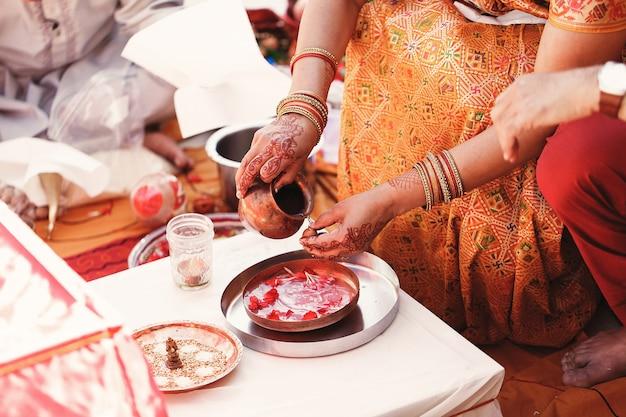 A noiva indiana lava nozes sobre o prato com espécies e pétalas