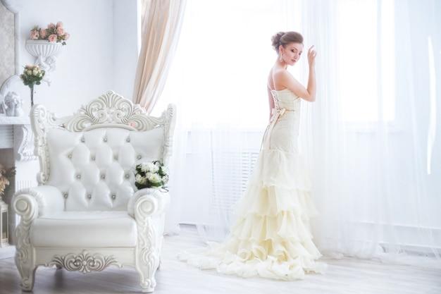 A noiva luxuosa deve se vestir na janela em um fundo claro.