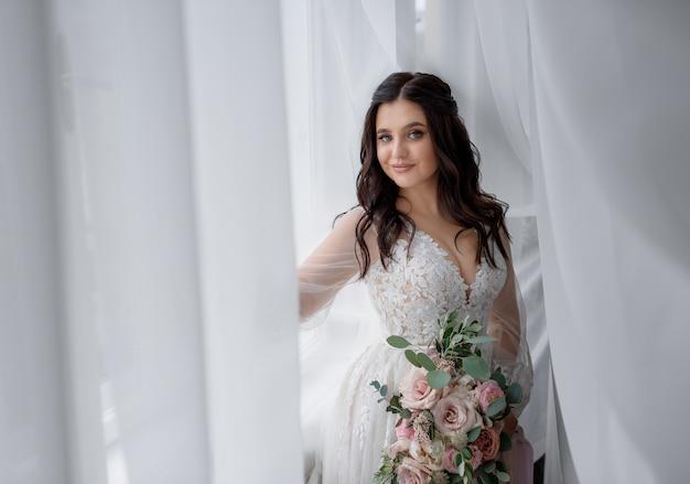 A noiva morena muito sorrida está segurando o buquê de casamento perto da janela e olhando direto