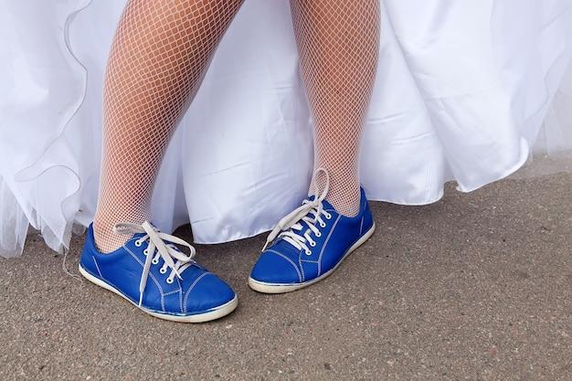 A noiva mostra sapatos de casamento brancos