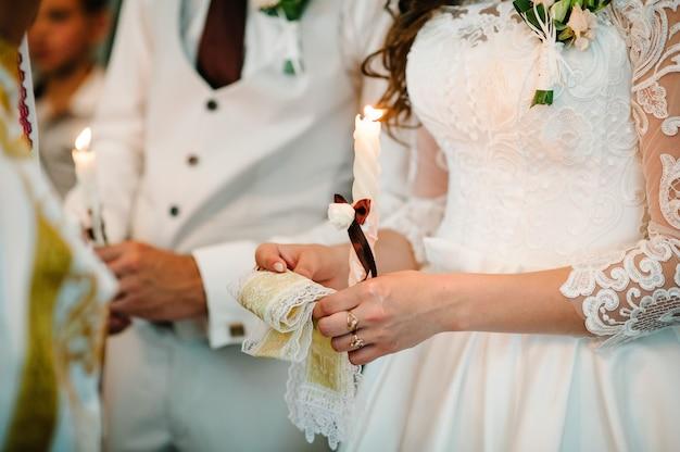 A noiva, o noivo tem nas mãos a vela do casamento. acender vela
