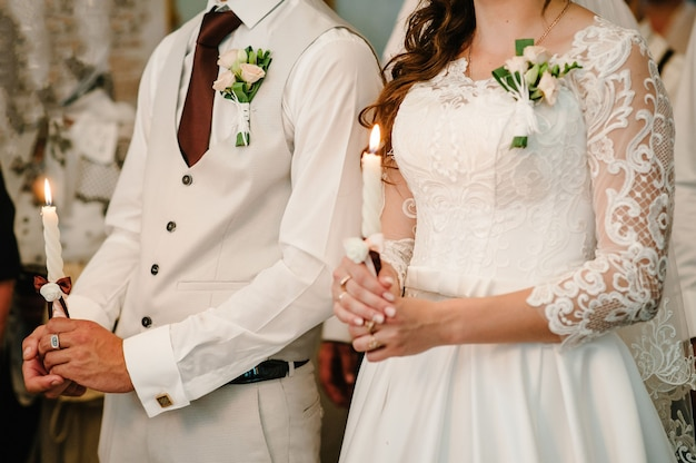 A noiva, o noivo tem nas mãos a vela do casamento. queime vela.