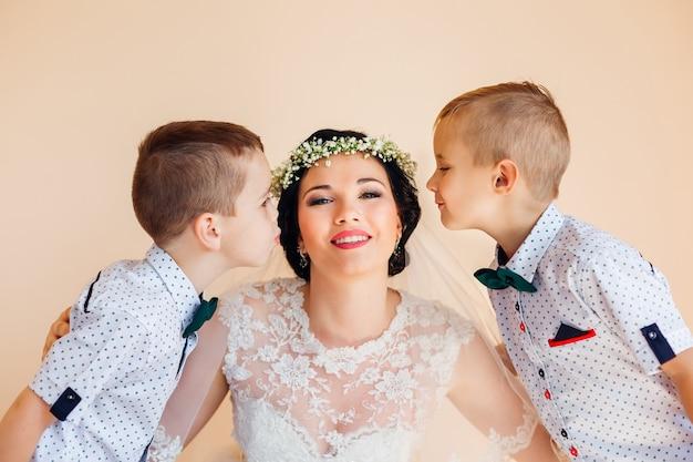 A noiva olha para a câmera e sorri meninos querem beijar a noiva no rosto