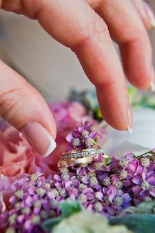 A noiva pega a mão de alianças de ouro com diamantes.