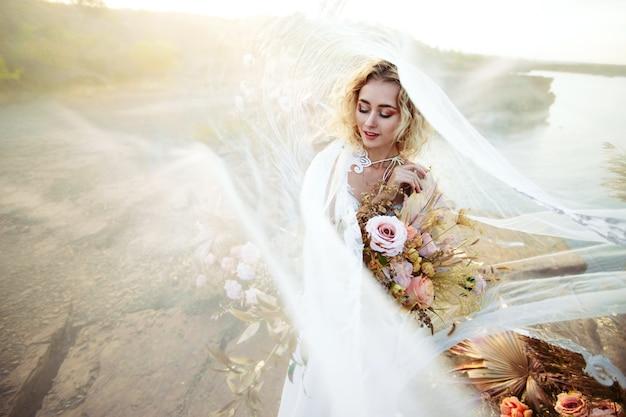 A noiva perto da decoração do casamento em uma cerimônia em um penhasco de rocha perto da água ao pôr do sol. véu voando com o vento