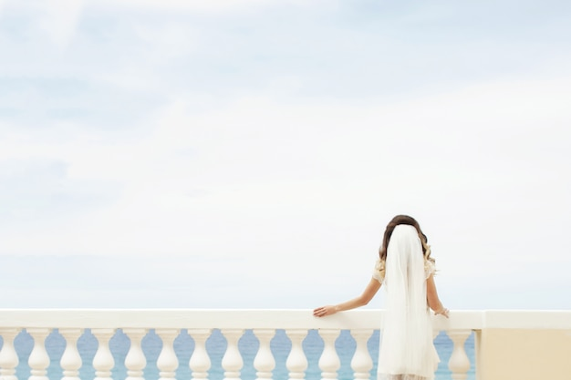 A noiva se inclina sobre uma varanda branca enquanto admira o mar