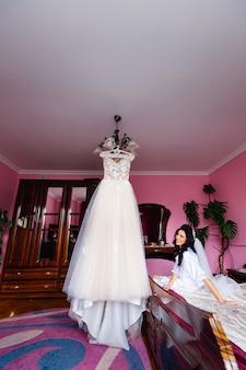 A noiva se senta em uma cama no quarto e olha para o casamento