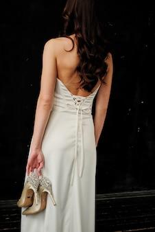 A noiva segura delicadamente nas mãos os sapatos de casamento.