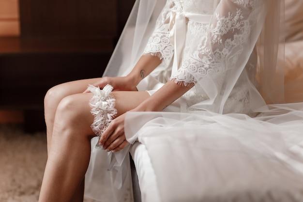 A noiva segura na mão liga perdida no quarto de hotel. conceito de casamento preparação manhã.