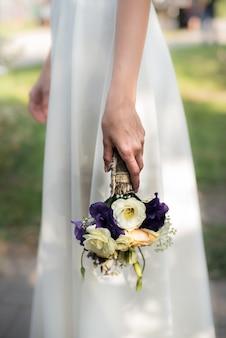 A noiva segura um buquê de casamento com flores roxas