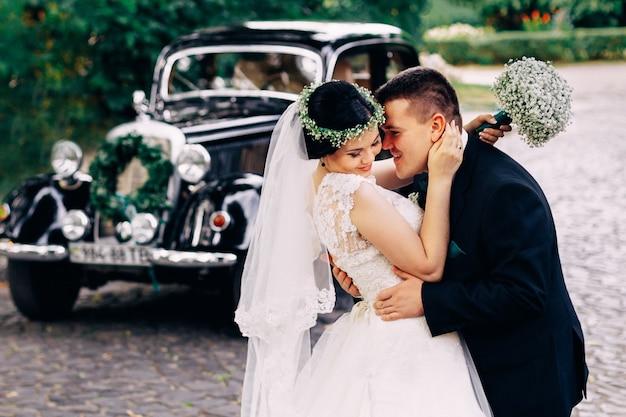 A noiva segura um buquê de casamento e o noivo a abraça perto de um carro retrô preto no par