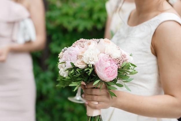 A noiva segura um lindo buquê de peônias