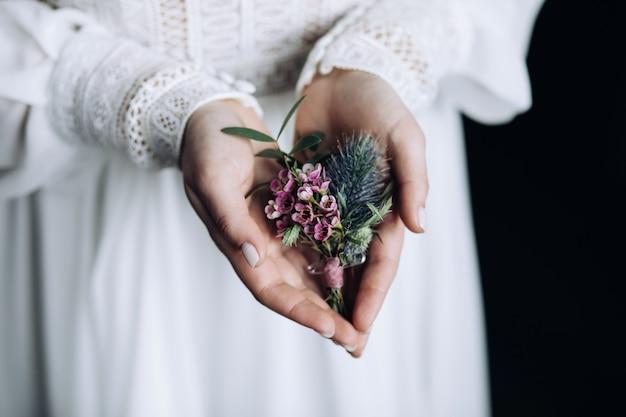 A noiva segura uma flor na lapela de flores cor de rosa nas palmas das mãos
