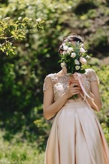 A noiva tem um buquê de casamento nas mãos dela