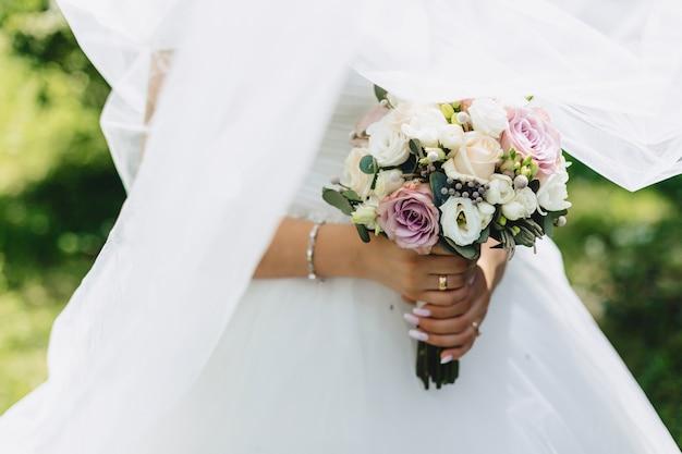 A noiva tem um buquê de casamento nas mãos