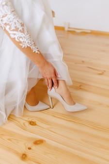 A noiva usa sapatos em uma manhã de casamento
