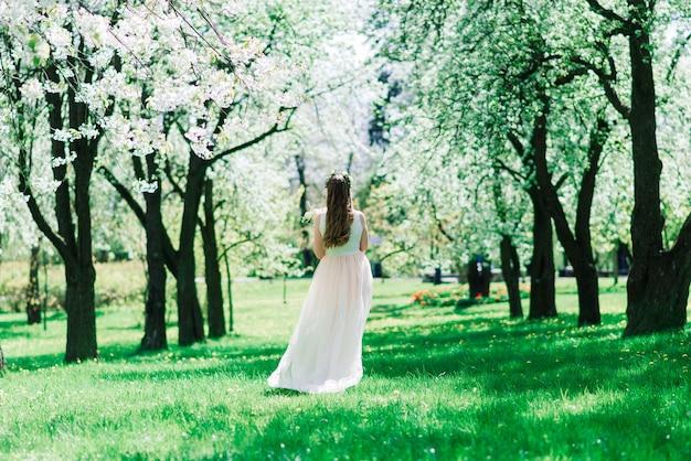 A noiva vestida de branco segurando um buquê no parque verde