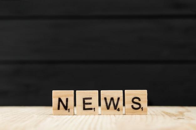 A notícia da palavra soletrada com letras de madeira
