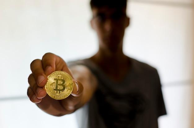 A nova maneira de como os jovens ganham dinheiro imagem de perto de um homem segurando a criptomoeda bitcoin