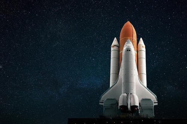 A nova nave espacial se prepara para decolar contra o pano de fundo de um céu estrelado azul. conceito de missão espacial. foguete voa para o espaço