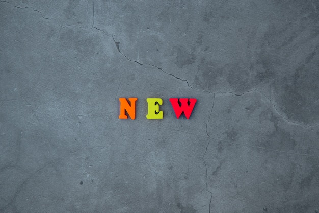 A nova palavra multicolorida é feita de letras de madeira em uma parede cinza rebocada.