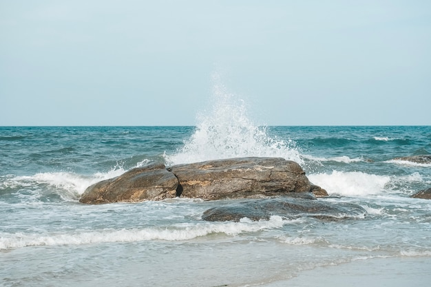 A onda do mar e espirra bate a pedra na praia de hua hin, prachuap khiri khan, tailândia. tom pastel.