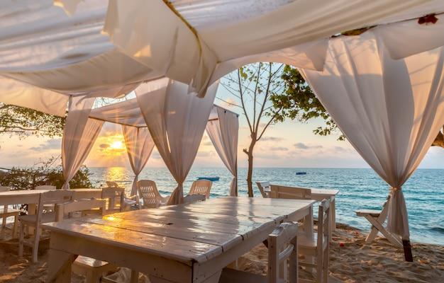 A opinião azul do mar da ilha com decorataion branco relaxa o lugar com iluminação do nascer do sol.