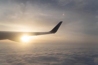 A opinião do cenário acima da asa da nuvem e do avião com por do sol. Veja embora a janela no avião.