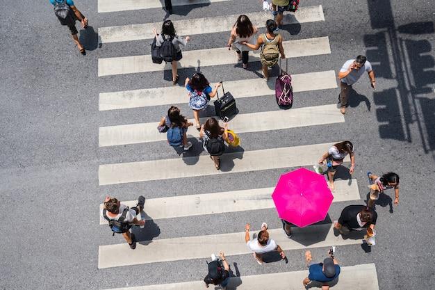 A opinião superior da foto aérea das pessoas anda na rua na cidade sobre a estrada do tráfego da passagem pedestre
