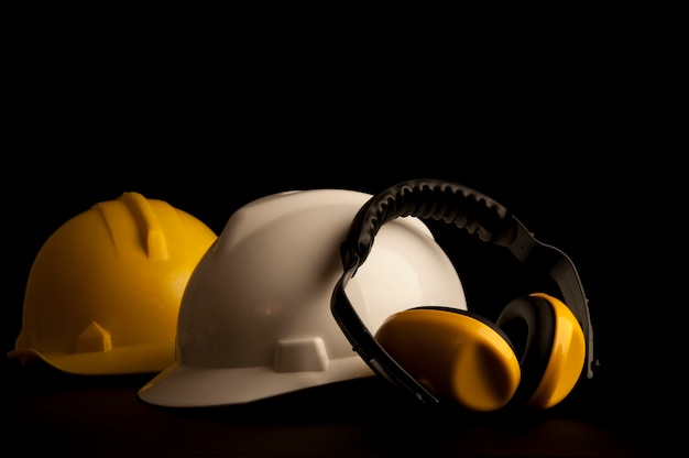 A orelha amarela muffs a segurança e os capacetes de couro no fundo preto.