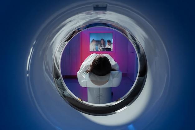 A paciente está deitada no tomógrafo e aguardando uma tomografia.