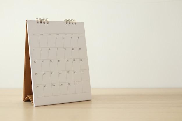 A página do calendário fecha na mesa de madeira com o fundo da parede branca.