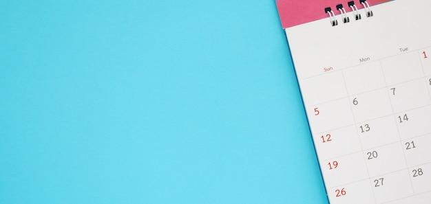 A página do calendário fecha-se no fundo azul planejamento de negócios, nomeação, conceito de reunião