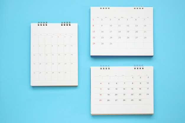A página do calendário fecha-se sobre o fundo azul, planejamento de negócios, compromisso, reunião