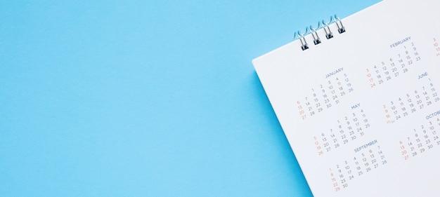 A página do calendário se fecha na mesa azul, planejamento de negócios, compromisso, reunião, conceito