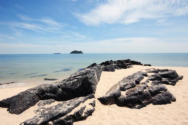 A paisagem bonita da praia rochosa e o mar acenam na beira-mar com o céu azul na praia de samila na tailândia