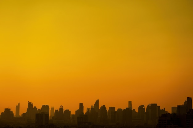 A paisagem da cidade mostra em silhueta o céu laranja com um amplo espaço para cópia