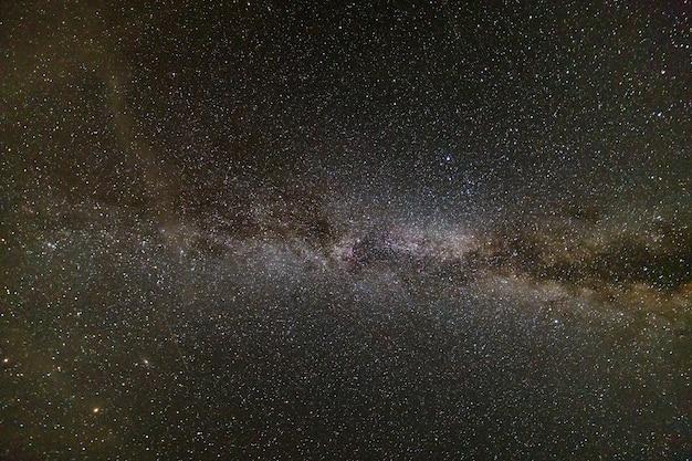 A paisagem da noite de milkyway com estrelas cobriu o céu.