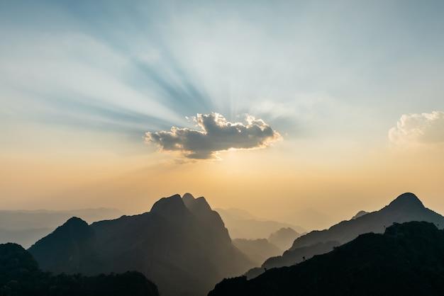 A paisagem das montanhas fica nublada com raios de sol e anoitecer perto do pôr do sol de doi luang chiang dao